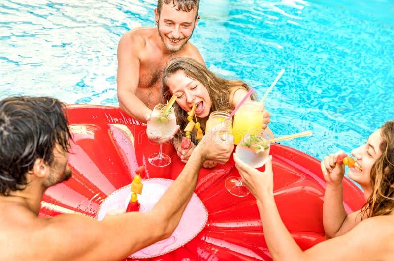 Vista lateral de los amigos felices que beben las ensaladas de fruta en la fiesta en la piscina que nada - concepto de las vacaci fotos de archivo