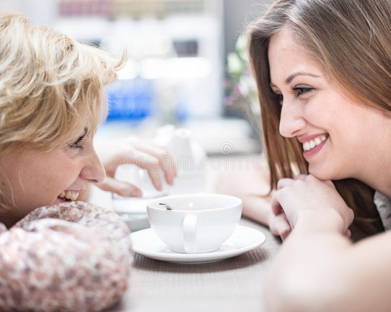 Vista lateral de los amigos femeninos jovenes sonrientes que miran uno a en café imagen de archivo