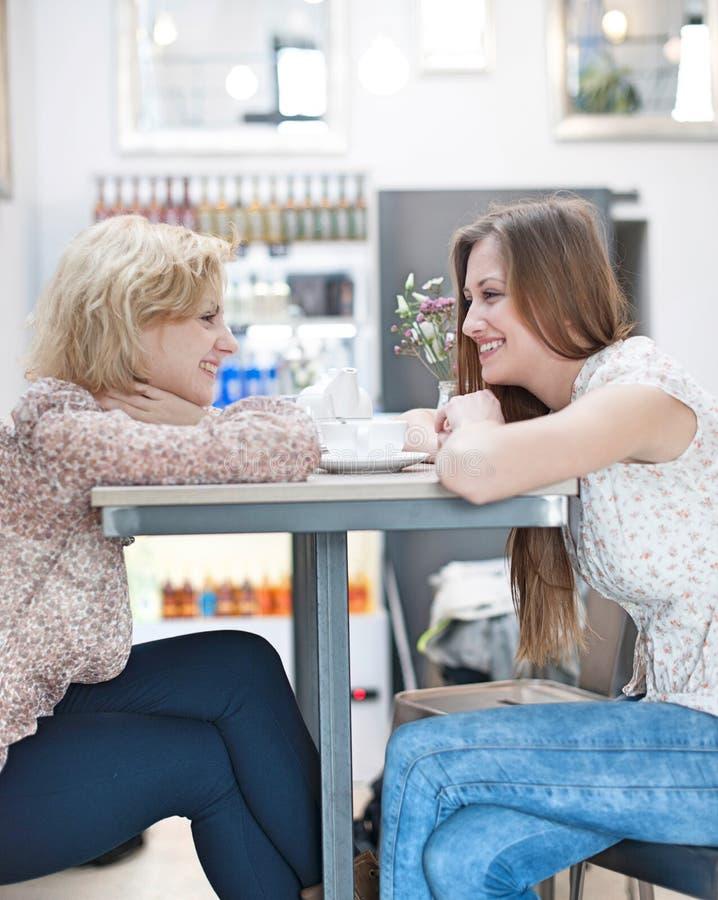 Vista lateral de los amigos femeninos jovenes sonrientes que se sientan en la tabla del café imagen de archivo libre de regalías