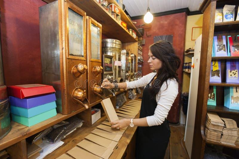 Vista lateral de los granos de café de dispensación del vendedor en bolsa de papel en la tienda fotos de archivo