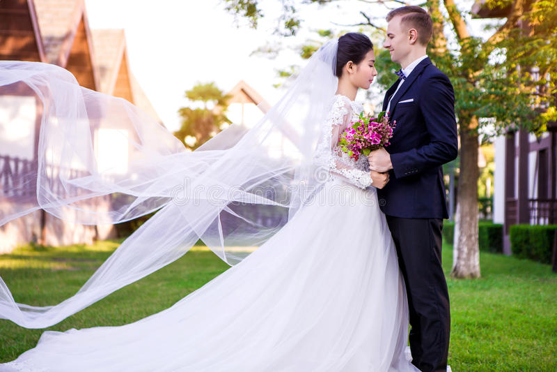 Vista lateral de los pares de la boda que se colocan en el césped imagenes de archivo