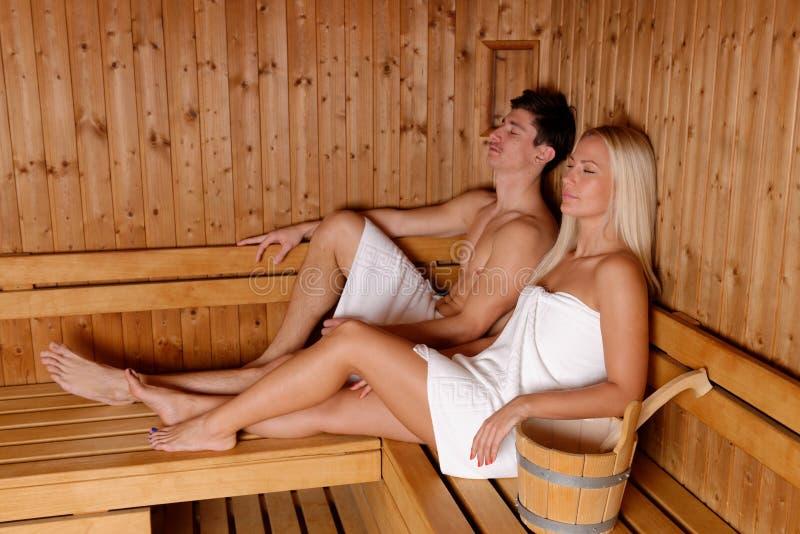 Pares jovenes que disfrutan de sauna imágenes de archivo libres de regalías