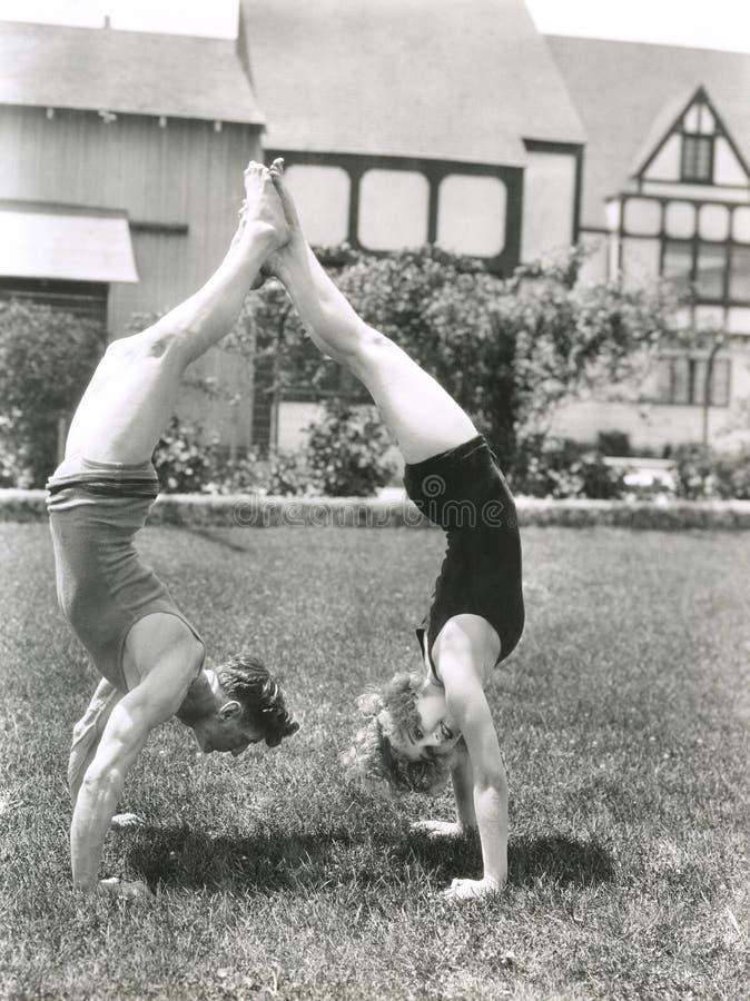 Vista lateral de los pares jovenes que hacen posiciones del pino en yarda fotos de archivo
