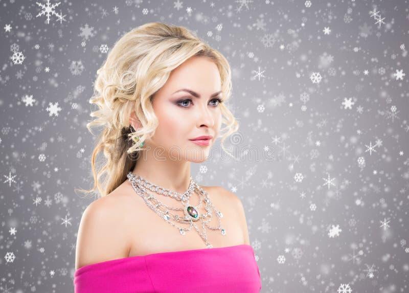 Vista lateral de louro bonito na colar vestindo do vestido cor-de-rosa com imagens de stock royalty free