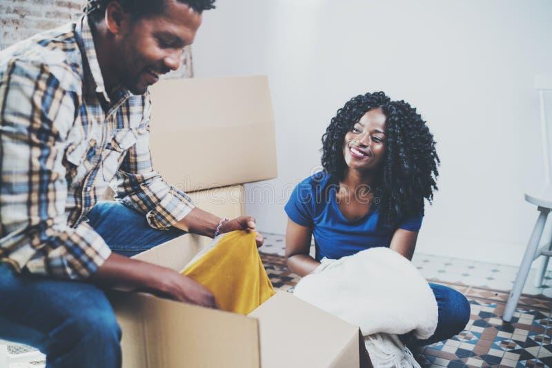 Vista lateral de pares africanos americanos negros jovenes con las cajas móviles en el nuevo apartamento Pares alegres que se sie imagenes de archivo