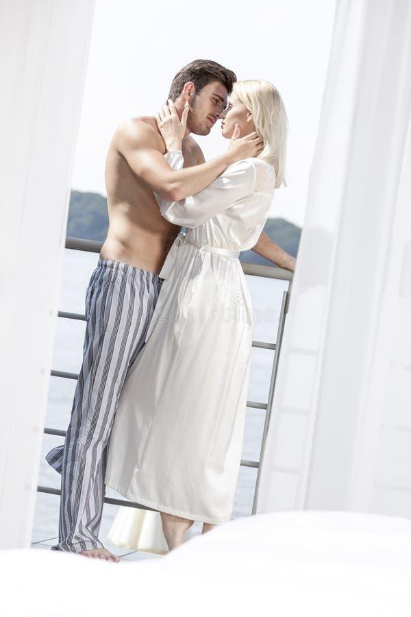 Vista lateral de pares jovenes románticos en tiempo de la calidad del gasto de la ropa de noche en balcón del hotel imagen de archivo