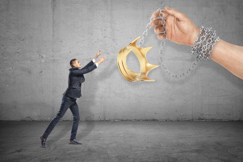 Vista lateral de poco hombre de negocios que alcanza hacia fuera para la corona del oro sostenida en cadena por la mano del hombr imagen de archivo