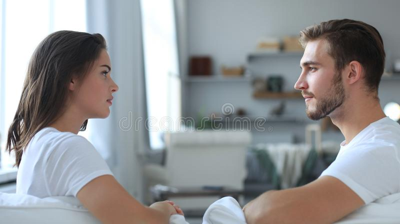 Vista lateral de sentarse que habla de los pares en un sofá y de mirarse en casa foto de archivo libre de regalías