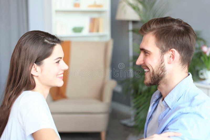 Vista lateral de sentarse que habla de los pares en un sof? y de mirarse en casa fotografía de archivo libre de regalías