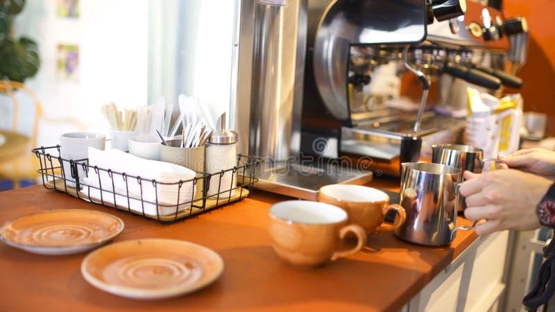 A vista lateral de um barista na camisa de manta azul prepara o cappuccino ou o latte em seu coffeeshop Arte Pondo o leite no fotos de stock
