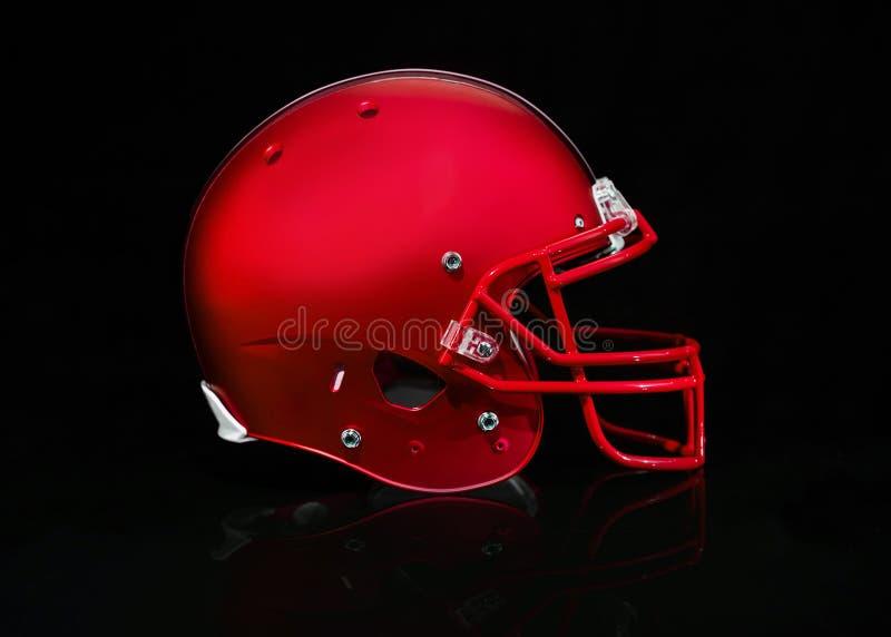 Vista lateral de um capacete de futebol vermelho em um fundo preto fotos de stock royalty free
