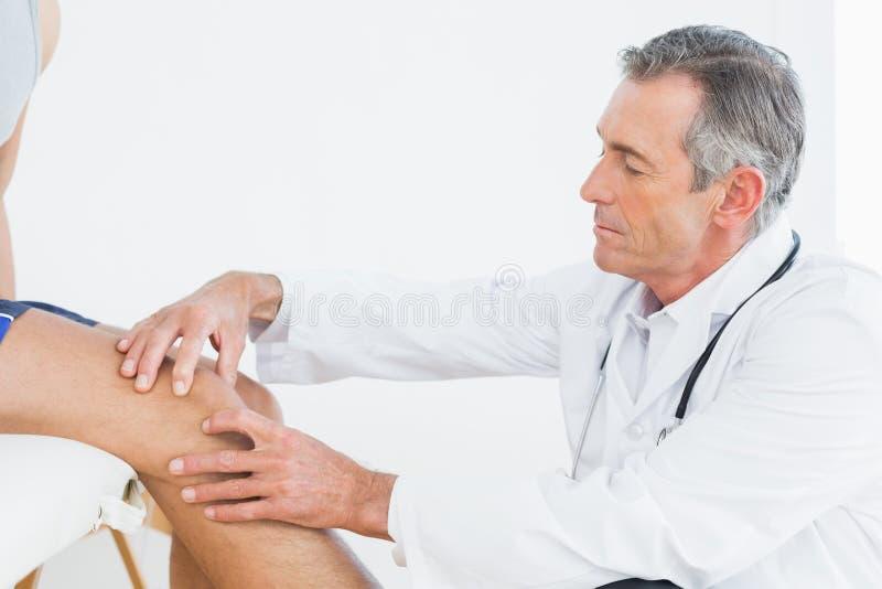 Vista lateral de um joelho de exame dos pacientes do doutor maduro fotografia de stock