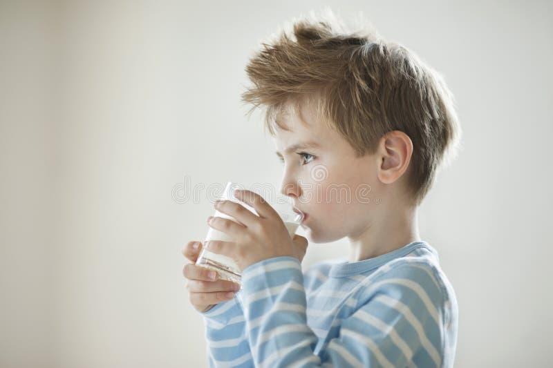 Vista lateral de um leite bebendo do menino novo imagens de stock