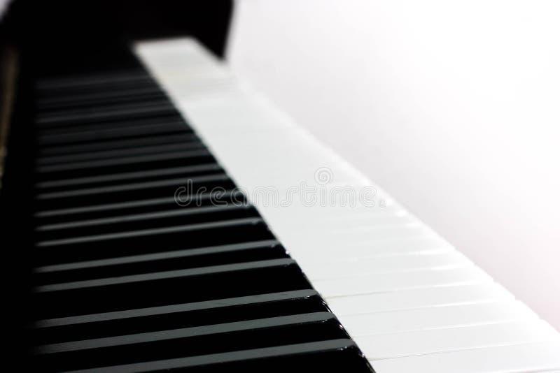 Vista lateral de um piano de madeira, telhas do piano em um fundo branco, isolado foto de stock