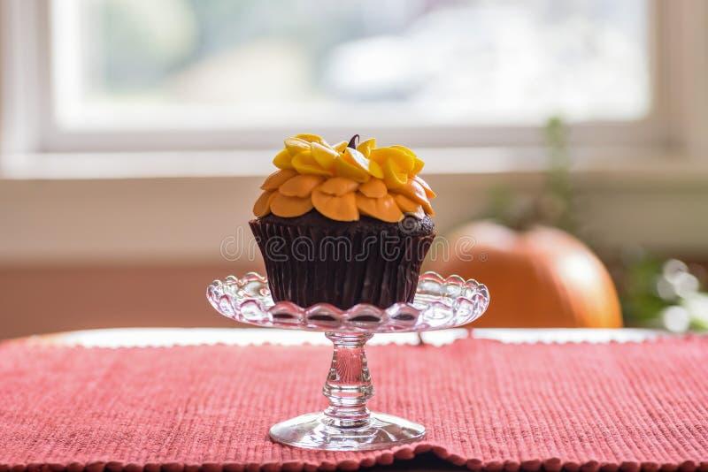 A vista lateral de um queque do chocolate em um suporte de vidro decorou wi fotografia de stock