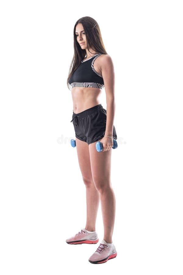 Vista lateral de uma jovem atlética fina que se encaixa olhando para baixo segurando sinos fotografia de stock