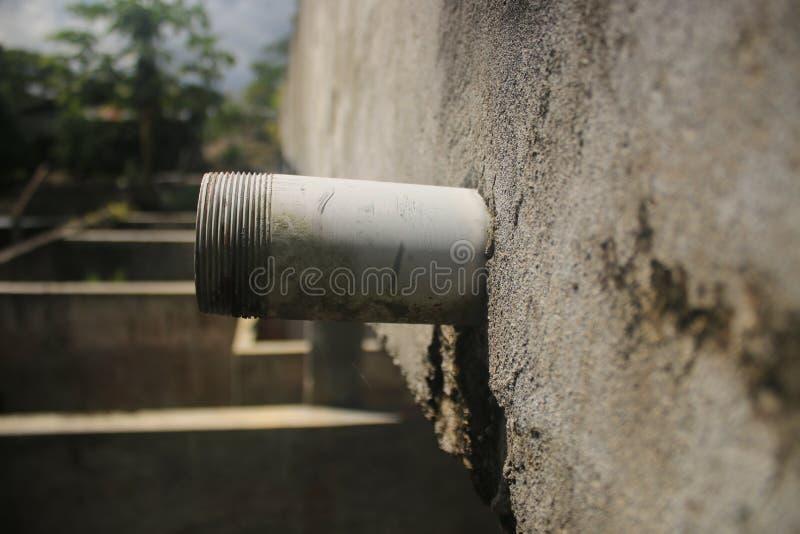 Vista lateral de uma tubula??o inacabado da drenagem que cola para fora uma parede cinzenta fotografia de stock