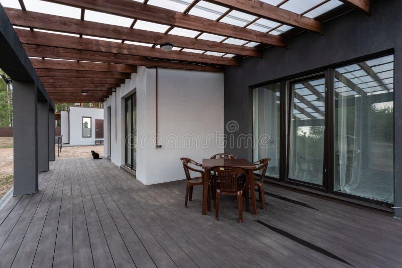 Vista lateral de uma varanda aberta na frente de uma casa de campo moderna da floresta A floresta nova do pinho sob o por do sol  foto de stock royalty free