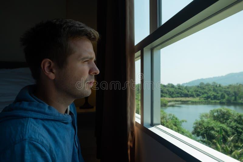 Vista lateral de un anhelo del hombre y mirada a través de ventana imagen de archivo