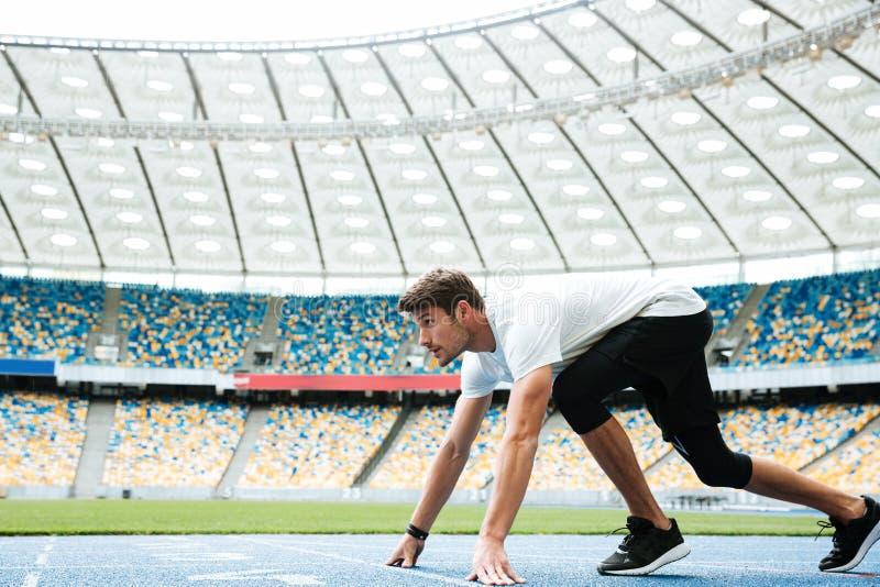 Vista lateral de un atleta joven en la posición de salida foto de archivo