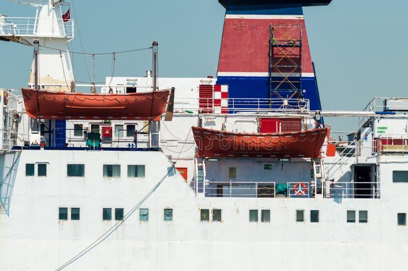 Vista lateral de un buque de pasajeros y de botes salvavidas anaranjados fotografía de archivo
