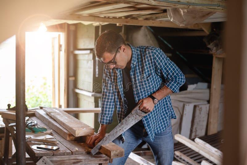 Vista lateral de un carpintero del hombre con los vidrios que asierran a un tablero de madera en el taller casero fotos de archivo libres de regalías