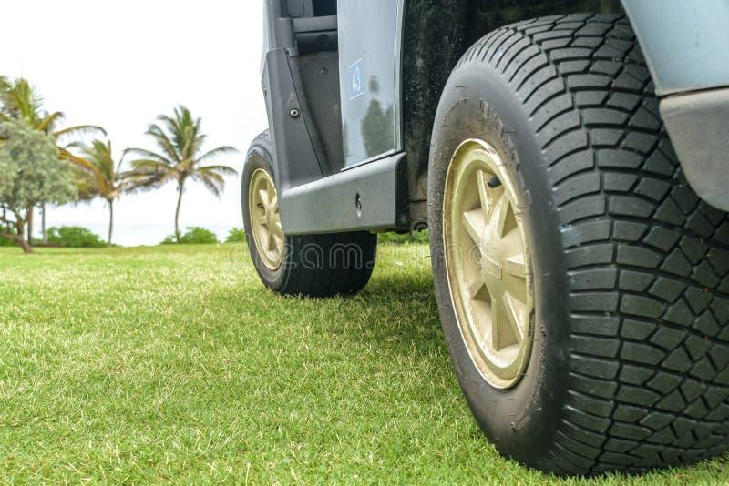 Vista lateral de un carro de golf verde parqueado en campo de golf fotos de archivo
