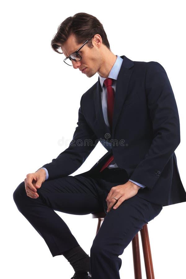Vista lateral de un hombre de negocios asentado con el pensamiento de los vidrios foto de archivo