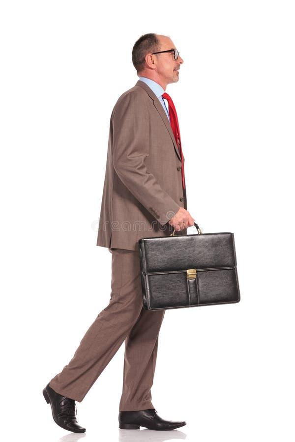 Vista lateral de un hombre de negocios mayor que celebra la maleta y caminar foto de archivo