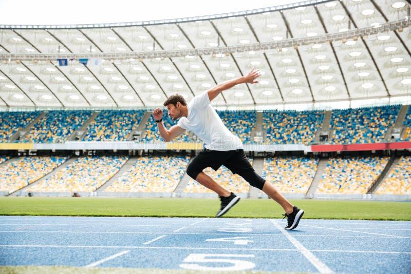 Vista lateral de un hombre del deporte que corre en una pista imágenes de archivo libres de regalías