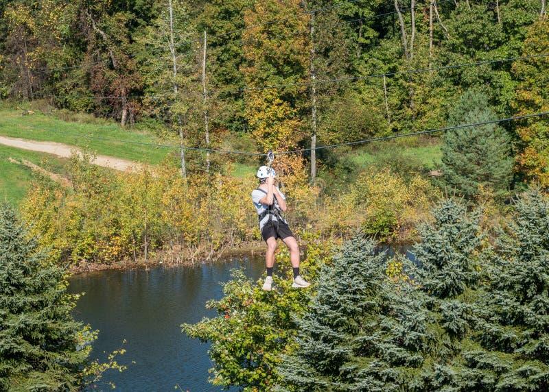 Vista lateral de un hombre en un zipline que va abajo de un valle en bosque fotografía de archivo