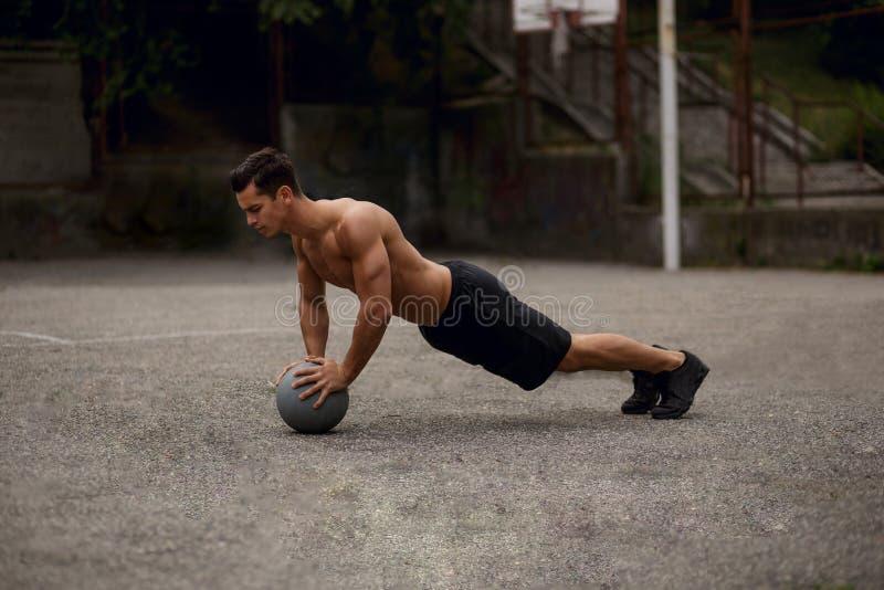 Vista lateral de un hombre joven atlethic, entonado que hace pectorales con un entrenamiento del baloncesto al aire libre en el a foto de archivo