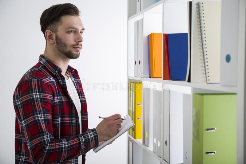 Vista lateral de un hombre joven barbudo serio en una biblioteca foto de archivo