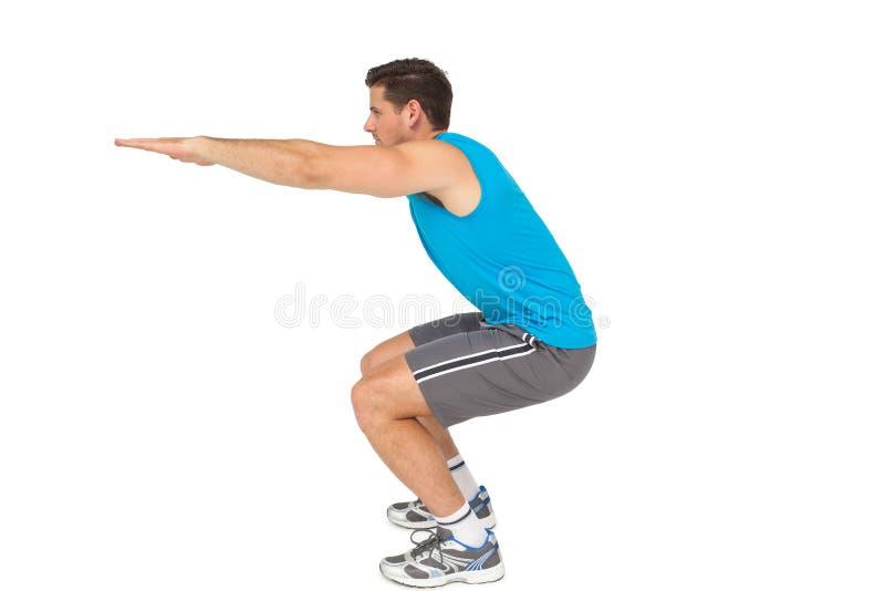 Vista lateral de un hombre joven del ajuste que hace estirando ejercicio fotos de archivo libres de regalías
