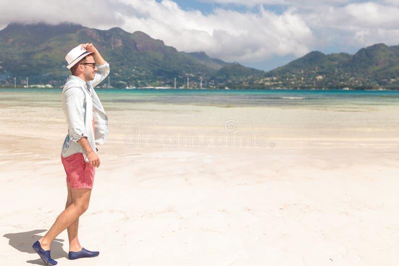 Vista lateral de un hombre joven que camina en la playa imagen de archivo libre de regalías