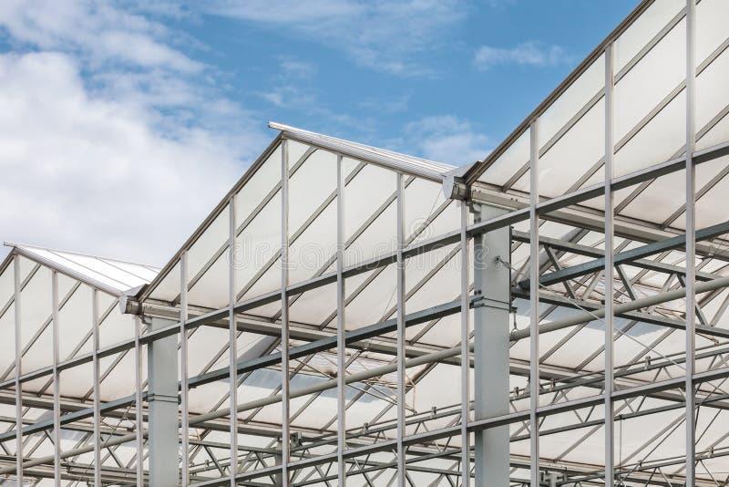 Vista lateral de un invernadero contra un cielo azul foto de archivo