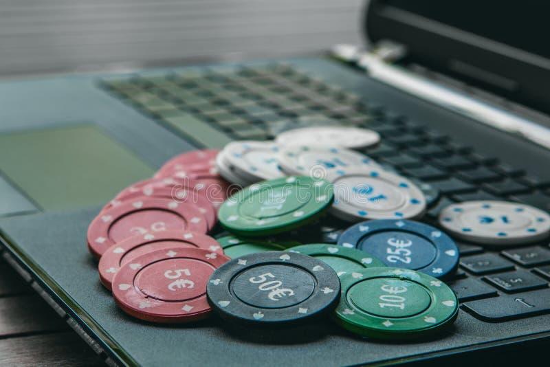 Vista lateral de un ordenador portátil con algunas tarjetas del póker Enviciado al concepto en línea del póker foto de archivo libre de regalías