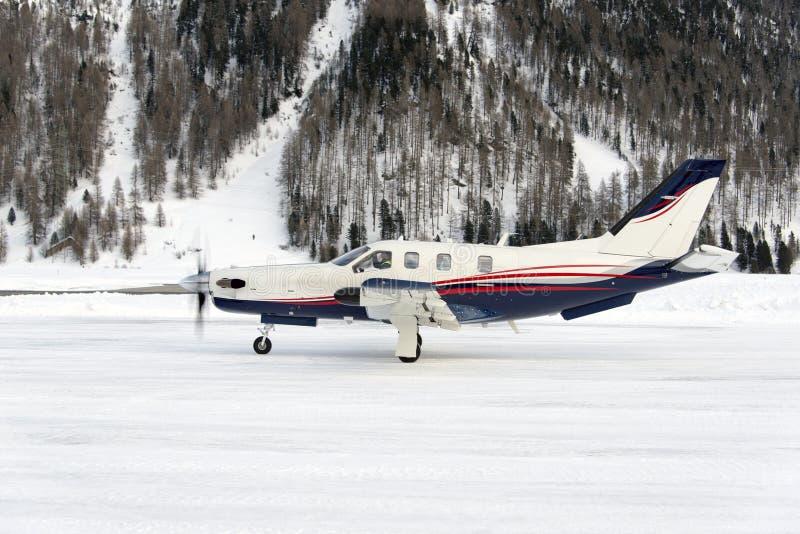 Vista lateral de un tipo avión privado del propulsor que saca en el aeropuerto nevoso de St Moritz Switzerland en invierno imagenes de archivo