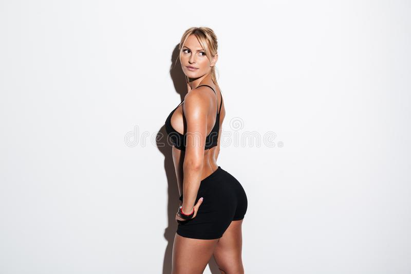 Vista lateral de una deportista sana que presenta y que mira lejos fotografía de archivo