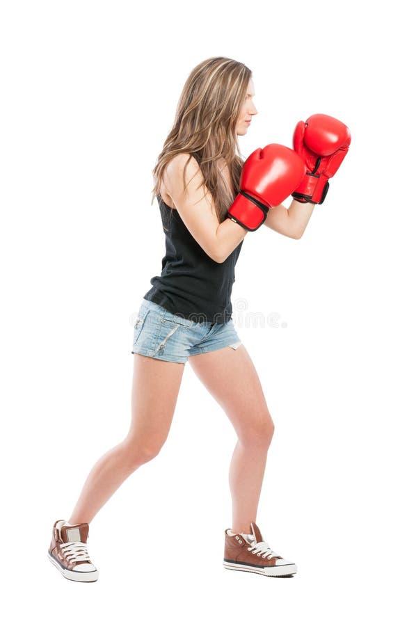 Vista lateral de una hembra que lleva guantes de boxeo rojos imagen de archivo libre de regalías