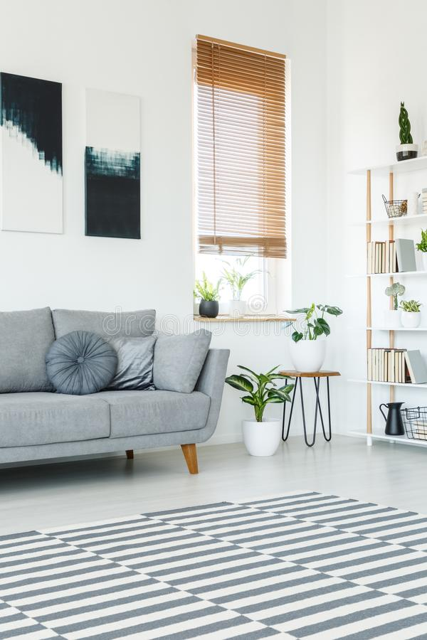 Vista lateral de una manta rayada en un interior brillante de la sala de estar con fotos de archivo libres de regalías