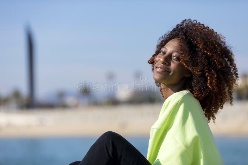 Vista lateral de una mujer afro rizada hermosa que se sienta en las rocas del rompeolas que r?en mientras que mira la c?mara al a fotos de archivo