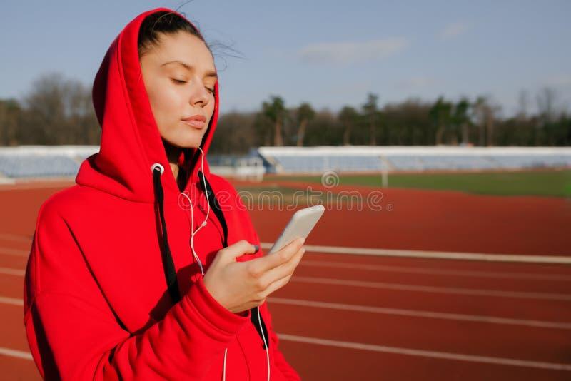 Vista lateral de una mujer joven del deporte que lleva una sudadera con capucha roja Él es que activa y que escucha la música con foto de archivo