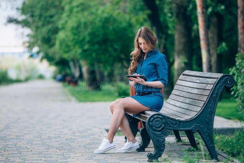 Vista lateral de una mujer joven que usa la tableta imagen de archivo