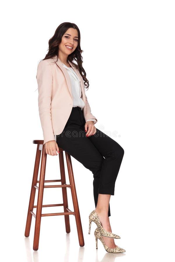 Vista lateral de una mujer de negocios sonriente joven asentada imágenes de archivo libres de regalías