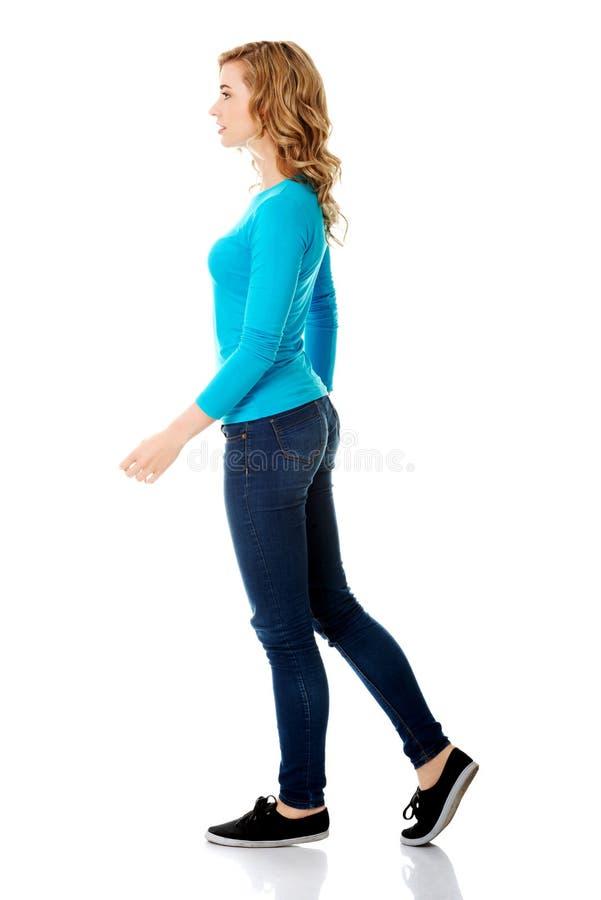 Vista lateral de una mujer que camina lentamente foto de archivo
