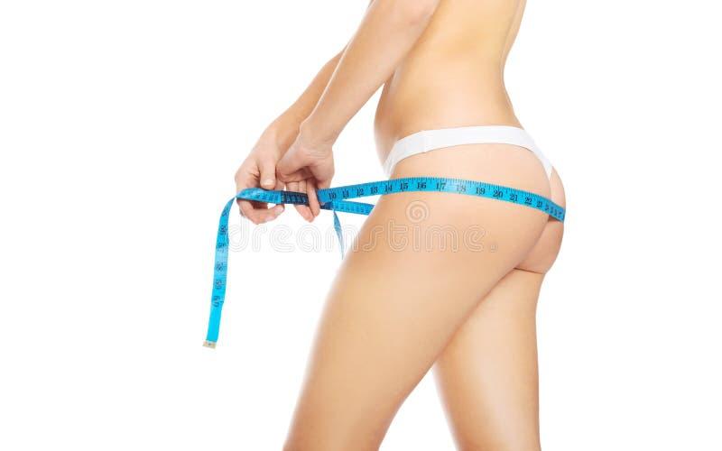 Vista lateral de una mujer que mide sus nalgas imagen de archivo
