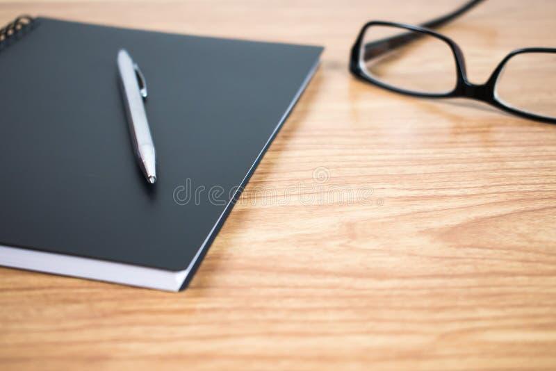 Vista lateral de una pluma y de un cuaderno en el listo en la tabla Cierre para arriba imagen de archivo libre de regalías