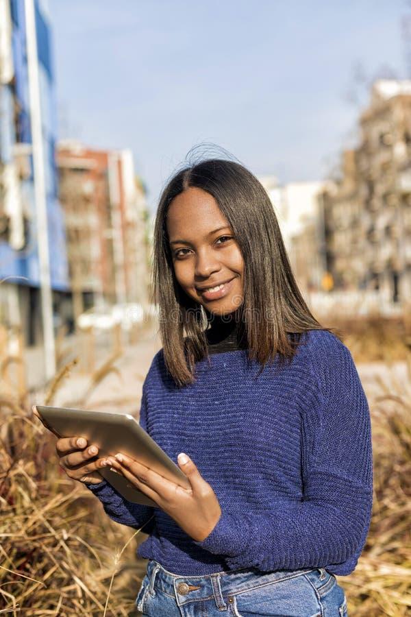 Vista lateral de una situación afroamericana de la muchacha, mientras que sostiene la tableta en sus manos y mira la cámara foto de archivo libre de regalías