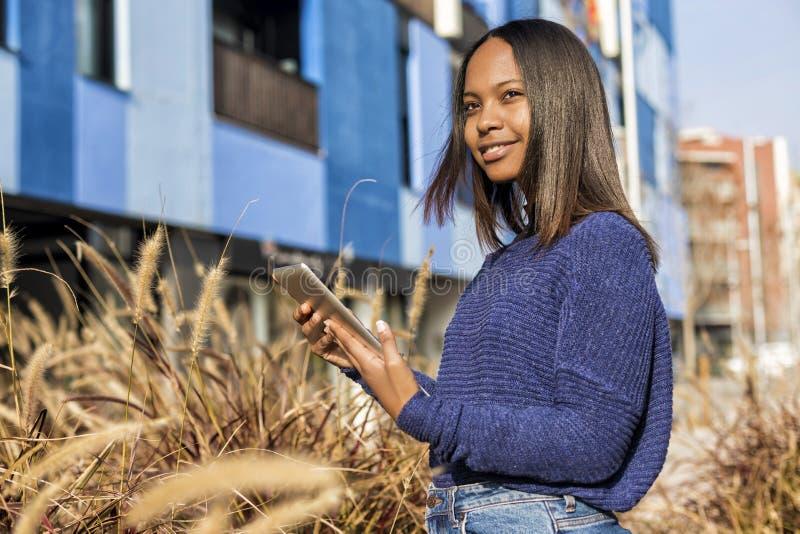 Vista lateral de una situación afroamericana de la muchacha, mientras que sostiene la tableta en sus manos y mira lejos foto de archivo